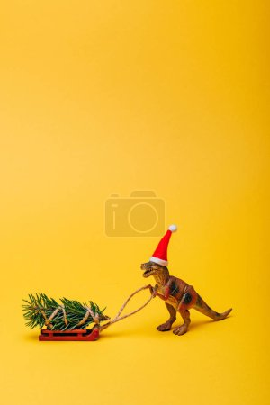 Toy dinosaur in santa hat with fir on sleigh on yellow background