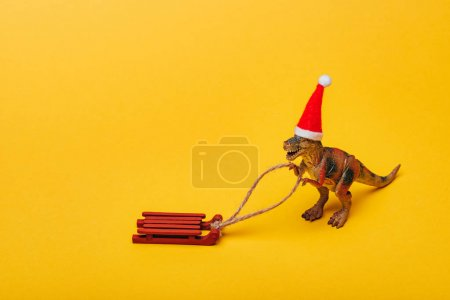 Toy dinosaur in santa hat with sleigh on yellow background