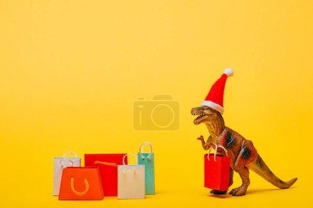 Photo pour Jouet dinosaure en santa chapeau avec des sacs à provisions sur fond jaune - image libre de droit