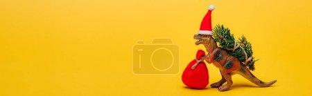 Photo pour Dinosaure jouet en santa avec sac et sapin sur fond jaune, photo panoramique - image libre de droit