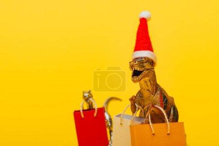 Photo pour Concentration sélective de dinosaures jouets dans un chapeau de Père Noël et des sacs à provisions sur fond jaune - image libre de droit