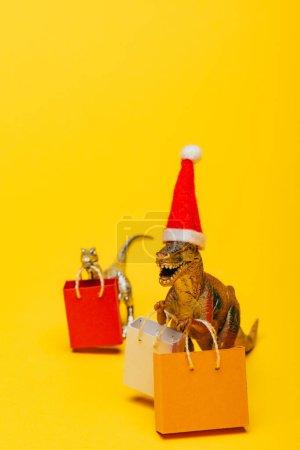 Foto de Selective focus of toy dinosaurs in santa hat and shopping bags on yellow background - Imagen libre de derechos
