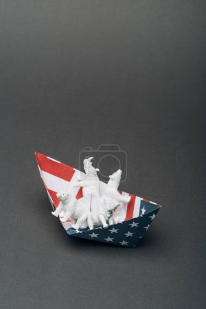 Photo pour White toy animals in paper boat from american flag on grey background, animal welfare concept - image libre de droit