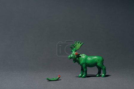 Зеленый игрушечный муз с рогом на сером фоне, концепция охоты на рога