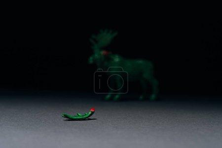 Селективный фокус рога с кровью и игрушечным лосем на сером фоне, охота за концепцией рогов