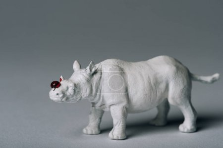 White toy rhinoceros with blood on grey background, hunting for horn concept
