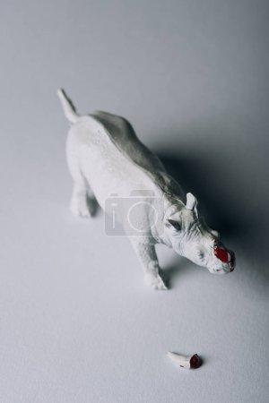 Draufsicht auf Horn mit Blut und Spielzeug-Nashorn auf grauem Hintergrund, Jagd nach Horn-Konzept