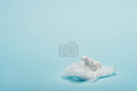 Photo for Toy polar bear on plastic packet on blue background, environmental pollution concept - Royalty Free Image