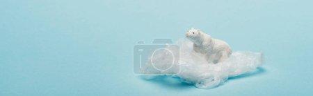 Photo pour Photo panoramique d'un ourson polaire jouet sur un paquet de plastique sur fond bleu, concept de pollution de l'environnement - image libre de droit