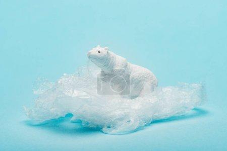 Photo pour Ours polaire jouet sur un paquet de plastique sur fond bleu, concept de pollution de l'environnement - image libre de droit