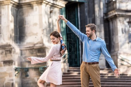 Photo for Couple of young, stylish tourists dancing on street in sunlight - Royalty Free Image