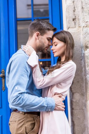 Photo for Happy young couple hugging while standing face to face near blue door - Royalty Free Image