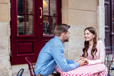 Photo for Happy young couple holding hands and looking at each other while sitting in street cafe - Royalty Free Image