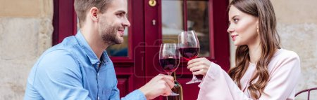 Photo for Panoramic shot of smiling couple sitting in street cafe and clinking glasses of red wine - Royalty Free Image