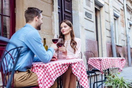 attractive young woman looking at boyfriend while sitting in street cafe and clinking glasses of red wine