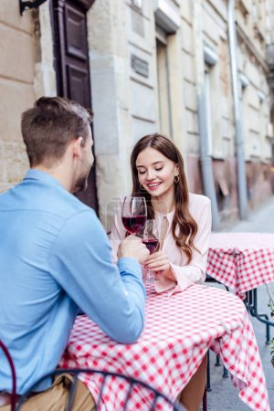 happy young woman clinking glasses of red wine with boyfriend while sitting in street cafe