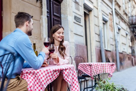 pretty young woman clinking glasses of red wine with boyfriend while sitting in street cafe