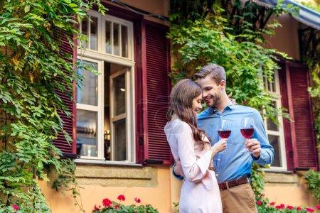 Foto de Feliz joven pareja sosteniendo vasos de vino tinto mientras está de pie cerca de la casa cubierta de hiedra verde - Imagen libre de derechos