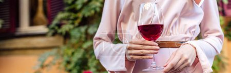 cropped view of woman holding glass of red wine, panoramic shot