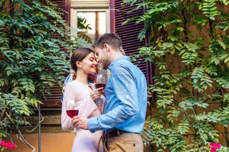 Photo pour Couple heureux embrassant les yeux fermés et tenant des verres de vin rouge tout en se tenant près de la maison couverte de lierre vert - image libre de droit