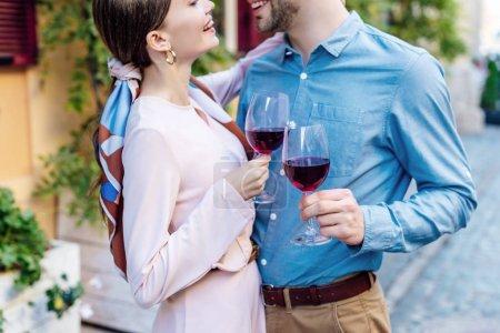 Photo pour Vue recadrée de couple heureux se regardant tout en tenant des verres de vin rouge - image libre de droit