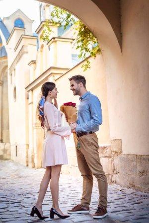 Photo pour Jeune homme présentant bouquet de roses tout en faisant la demande en mariage à petite amie dans la rue - image libre de droit