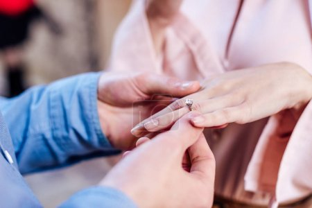 Photo pour Vue recadrée de l'homme mettant bague de mariage sur le doigt de la petite amie - image libre de droit