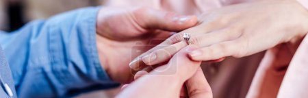 Photo pour Vue recadrée de l'homme mettant l'anneau de mariage sur le doigt de la petite amie, plan panoramique - image libre de droit