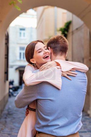 Photo pour Heureuse jeune femme embrassant petit ami dans la rue avec les yeux fermés - image libre de droit