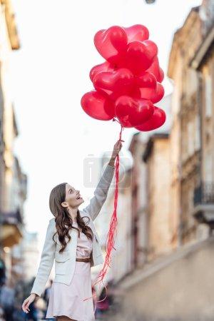Photo pour Fille gaie levant les yeux tout en tenant un tas de ballons rouges en forme de coeur sur la rue - image libre de droit