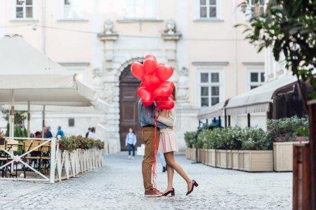 Photo pour Heureux jeune couple embrasser tout en se cachant derrière des ballons rouges en forme de coeur sur la place de la ville - image libre de droit