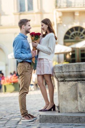 Photo pour Bel homme présentant bouquet de roses à petite amie heureuse dans la rue - image libre de droit