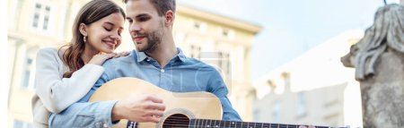 Photo for Panoramic shot of happy girl leaning on shoulder of boyfriend playing acoustic guitar - Royalty Free Image