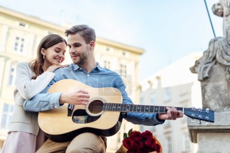 Photo pour Happy girl leaning on shoulder of boyfriend playing acoustic guitar on street - image libre de droit