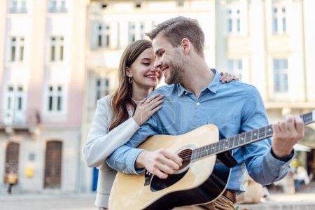 Photo pour Bel homme jouant de la guitare acoustique près d'une jolie copine dans la rue - image libre de droit