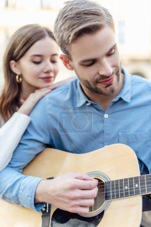 Photo pour Focus sélectif du bel homme jouant de la guitare acoustique quasi jolie copine - image libre de droit