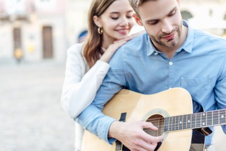 Photo for Selective focus of young man playing acoustic guitar near happy girlfriend - Royalty Free Image