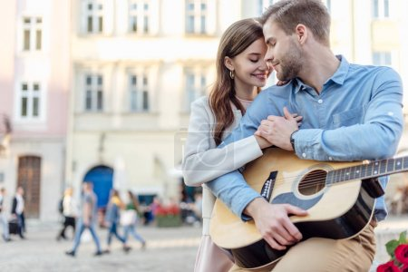 Photo for Happy girl embracing boyfriend holding acoustic guitar on street - Royalty Free Image
