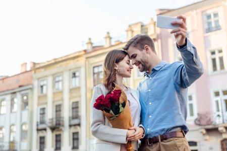 Photo pour Heureuse jeune femme tenant bouquet de roses tout en souriant petit ami prendre selfie sur smartphone - image libre de droit