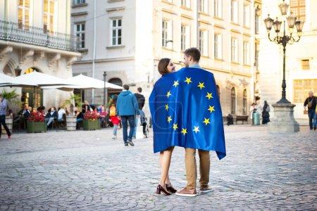 Photo pour Couple de jeunes touristes, enveloppé dans le drapeau de l'union européenne, debout sur la place de la ville - image libre de droit