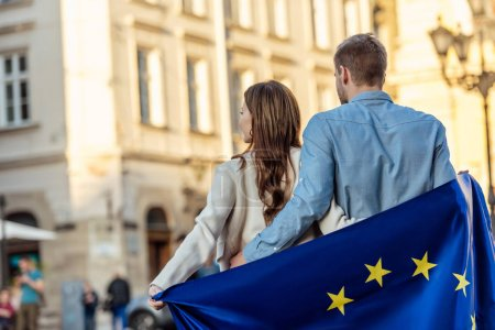 Photo pour Vue arrière du jeune couple, enveloppé dans le drapeau de l'union européenne, debout dans la rue - image libre de droit