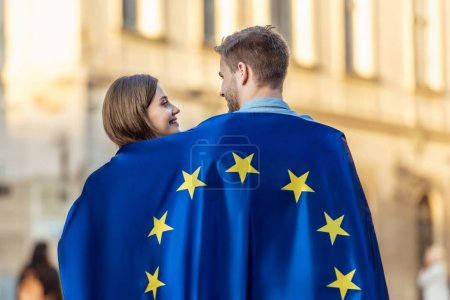 young couple of tourists, wrapped in flag of european union, looking at each other on street