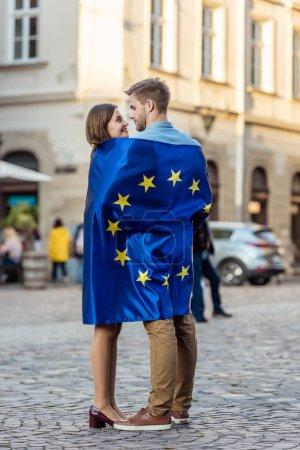 Photo pour Touristes heureux, enveloppés dans le drapeau de l'union européenne, se regardant dans la rue - image libre de droit