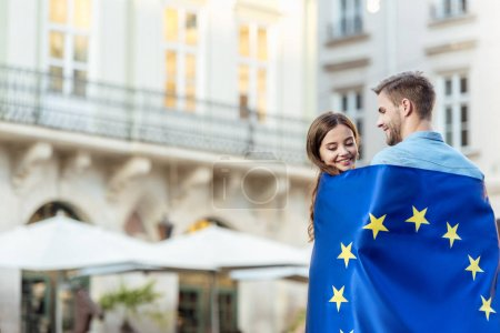 young, smiling couple of tourists wrapping in flag of european union on street