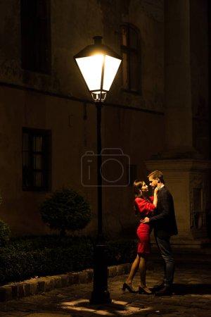 Photo pour Un couple jeune et élégant se blottit la nuit sous un lampadaire - image libre de droit