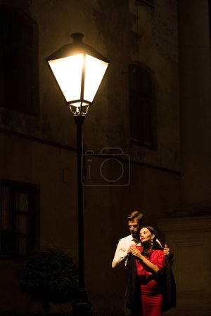 Photo for Young man covering frozen girlfriend with jacket while standing under street lamp at night - Royalty Free Image