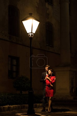 Photo for Young man embracing elegant, frozen girlfriend while standing under street lamp at night - Royalty Free Image