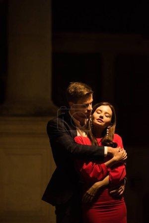 Photo pour Jeune homme embrassant une élégante copine dans la rue la nuit - image libre de droit