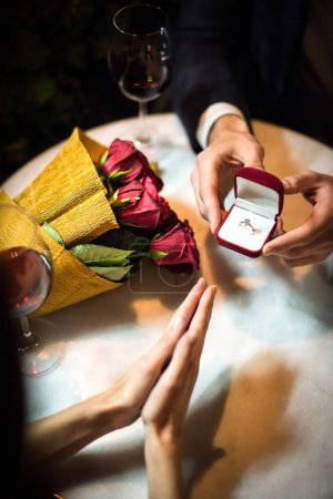 Photo for Cropped view of man presenting wedding ring to girlfriend while making marriage proposal - Royalty Free Image