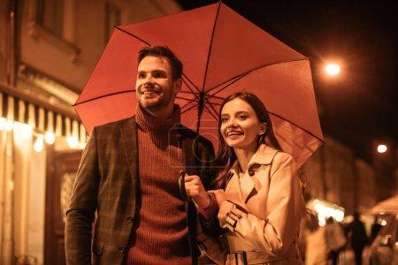 Photo pour Happy couple en costume d'automne marchant sous le parapluie dans la rue du soir - image libre de droit